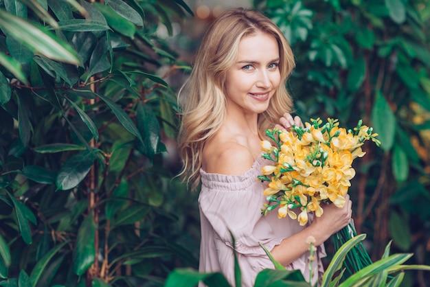 繊細な黄色のフリージアを手に持って植物の近くに立って魅力的な若い女性 無料写真
