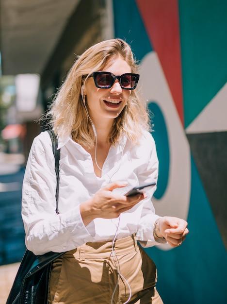 日光の下で携帯電話を使用してサングラスをかけている魅力的な若い女性 無料写真