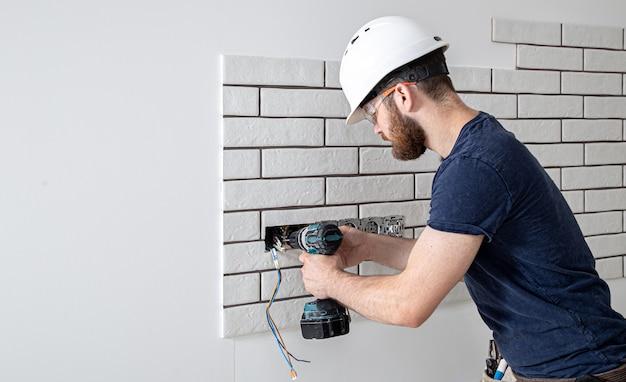Электрик-строитель в комбинезоне с дрелью во время установки розеток. концепция ремонта дома. Бесплатные Фотографии