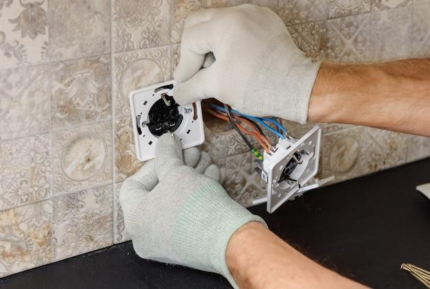 Электрик устанавливает на стене выключатели и розетки. Premium Фотографии