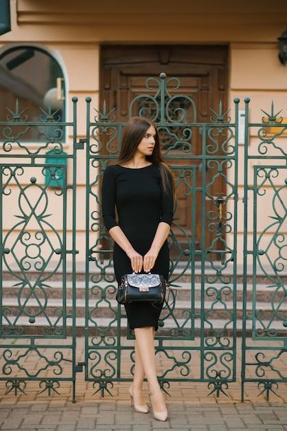 黒のドレスを着たエレガントな女の子が手にバッグを持ち、家の錬鉄製の門の近くに立つ Premium写真
