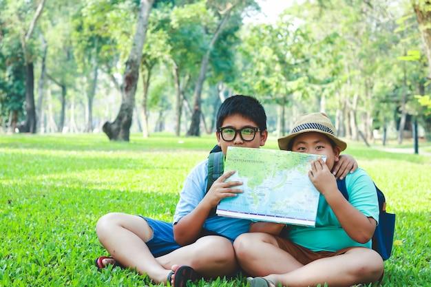 Элементарный азиатский мальчик сидя на лужайке в саде держа карту для того чтобы изучить информацию. Premium Фотографии