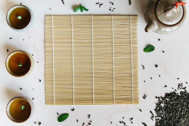 Поднятый вид травяных чашек с подставкой для столовых приборов; чайник и сухие листья на белом фоне Premium Фотографии