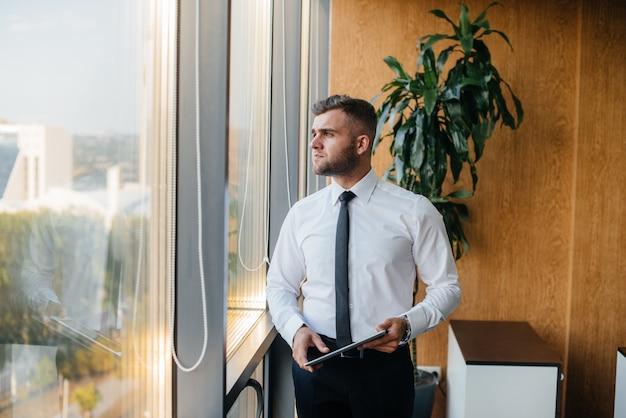 Сотрудник в офисе стоит возле окна. финансов Premium Фотографии