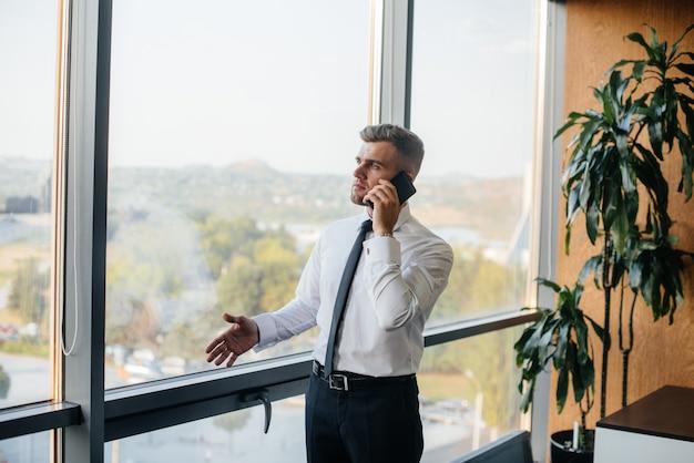 Сотрудник в офисе стоит возле окна. финансы. Premium Фотографии