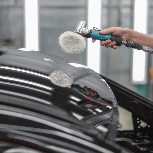 Сотрудник полирует окрашенную поверхность автомобиля Premium Фотографии