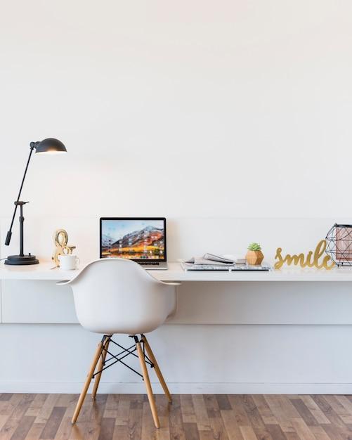 ノートパソコンと展示品を机の前に空の白い椅子 Premium写真