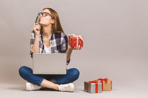 Взволнованная случайная девочка, держащая ноутбук и кредитную карту, сидя на полу со стопкой подарочных коробок Premium Фотографии