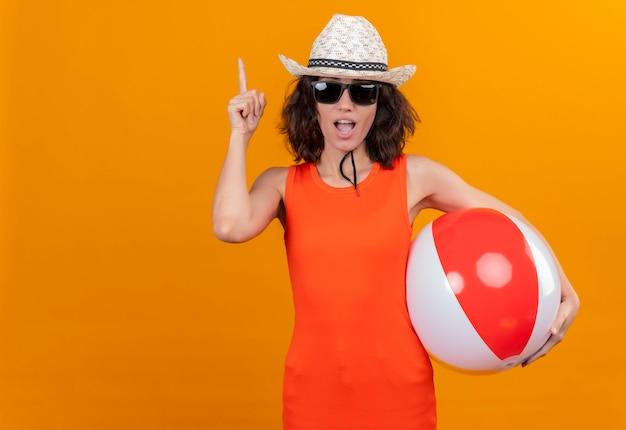 검지 손가락으로 가리키는 풍선 공을 들고 태양 모자와 선글라스를 착용하는 주황색 셔츠에 짧은 머리를 가진 종료 된 젊은 여자 무료 사진