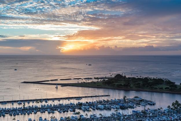 アラ・ワイ・スモール・ボート・ハーバーとマジック・アイランドからのヨットの広大な夕日 Premium写真