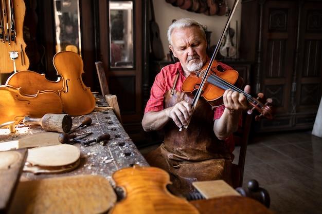 革のエプロンを身に着け、バイオリンを弾く彼の木工ワークショップに座っている経験豊富な白髪の年配の男性木工職人 無料写真