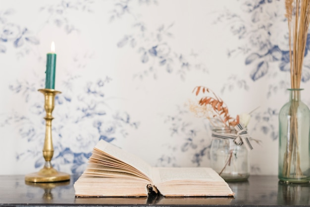 An illuminated candle and book on desk against wallpaper Free Photo