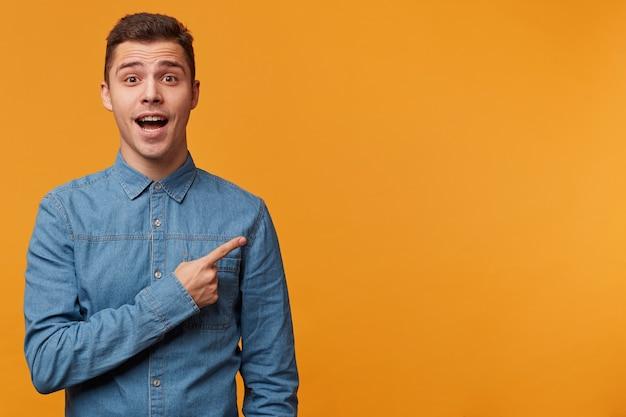 Вдохновленный молодой человек в джинсовой рубашке просит обратить внимание на что-то очень интересное Бесплатные Фотографии