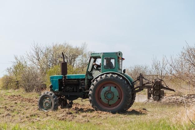 古い青いトラクターが畑を耕して土壌を耕します。 Premium写真