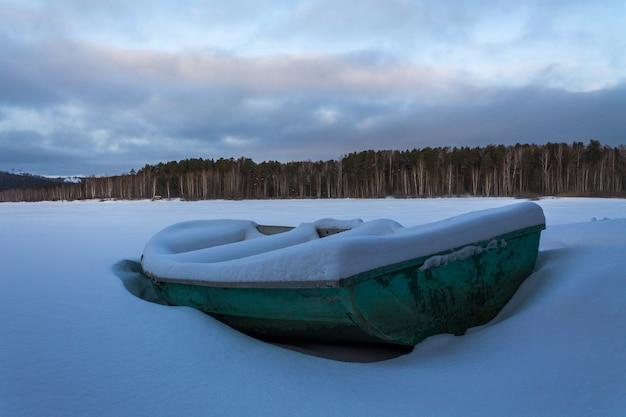 Старая зеленая шлюпка в замороженном озере. лодка покрыта чистым снегом Premium Фотографии
