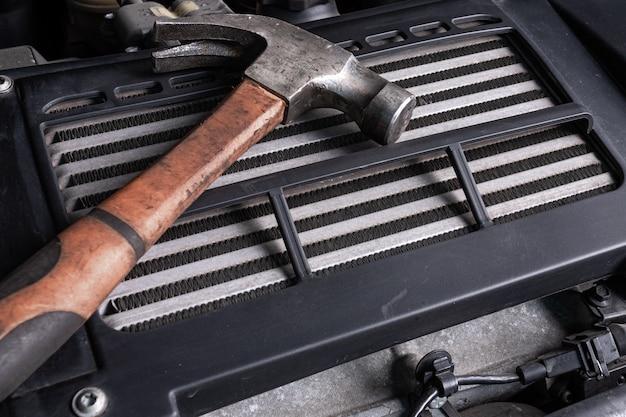 Старый металлический молоток лежит под капотом автомобиля на масляном радиаторе. концепция ремонта автомобилей и инструменты в автосервисе Premium Фотографии