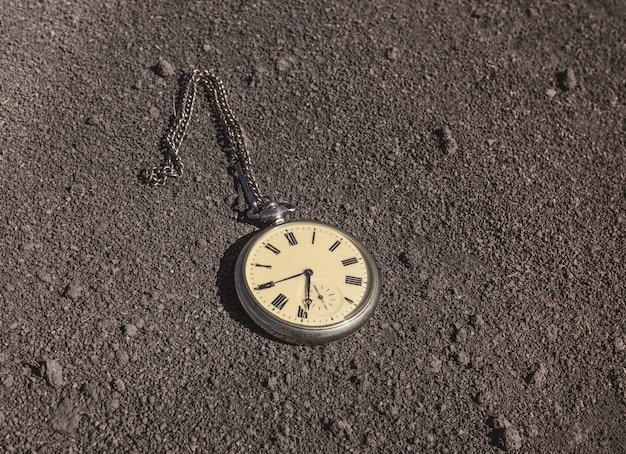 오래된 회중 시계가 마른 땅에 놓여 있습니다. 과거와 미래 시제. 프리미엄 사진