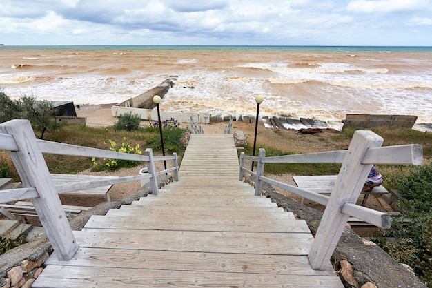 Старая деревянная лестница с перилами, ведущая к морскому пляжу волны на безлюдном море Premium Фотографии
