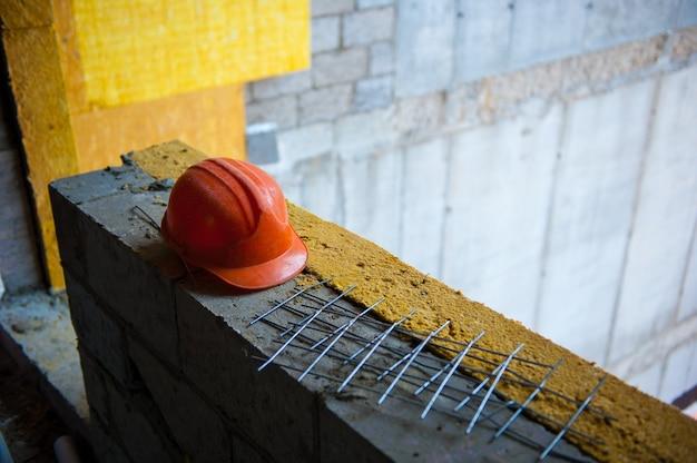 Оранжевый шлем строителя лежит на кирпичной кладке на стройплощадке Premium Фотографии