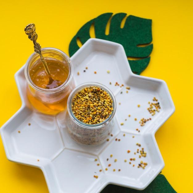 Верхний вид пыльцы пчел и мед в белом лотке на желтом фоне Бесплатные Фотографии