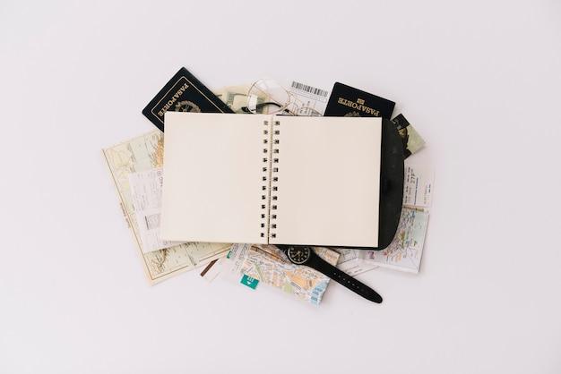 パスポートと白い背景にマップで空白のスパイラルノートブックのオーバーヘッドビュー 無料写真