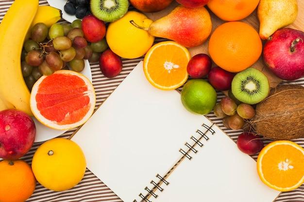 多くのカラフルなフルーツと空白の白いスパイラルメモ帳のオーバーヘッドビュー Premium写真