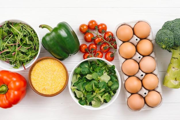 新鮮な野菜の俯瞰。卵と白い木製の机の上のポレンタ 無料写真
