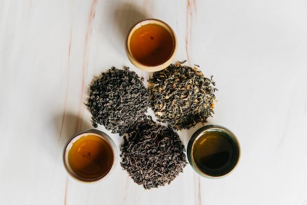 Вид сверху на травяные чашки с разнообразием сухих чайных листьев на мраморном фоне Premium Фотографии