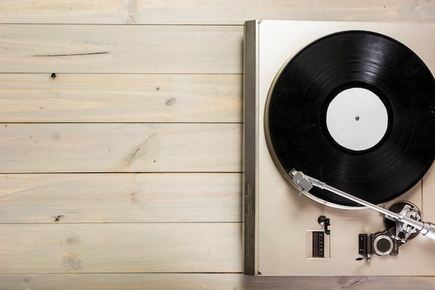 An overhead view of turntable vinyl record player on wooden table Free Photo