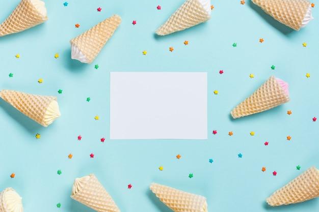 Вид сверху вафельных конусов и брызгает в окружении белой бумаги на синем фоне Бесплатные Фотографии