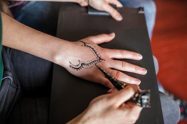 Вид сверху женщины, делающей татуировку хины от художницы Бесплатные Фотографии
