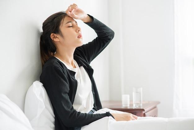不快な女性がベッドに座り、テーブルに薬を置いています。 無料写真
