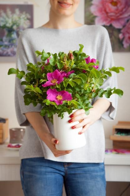 정체 불명의 모호한 젊은 여성이 아름다운 분홍색 꽃이 만발한 로즈힙과 함께 그녀의 손에 꽃병을 보유하고 있습니다. 실내 장식 및 사육실 식물의 개념 프리미엄 사진