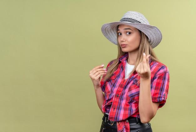 Расстроенная милая молодая женщина в клетчатой рубашке в шляпе, не показывающая денежного жеста рукой Бесплатные Фотографии