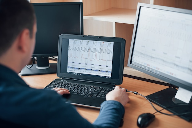Analisi delle informazioni. l'esaminatore del poligrafo lavora in ufficio con l'attrezzatura della sua macchina della verità Foto Gratuite