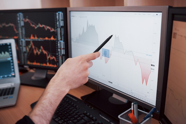 Analyzing data. close-up of young businessman pointing on the data presented in the chart with pen while working in creative office Premium Photo