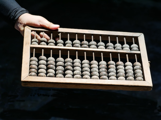 Ancient chinese abacus on hand Premium Photo