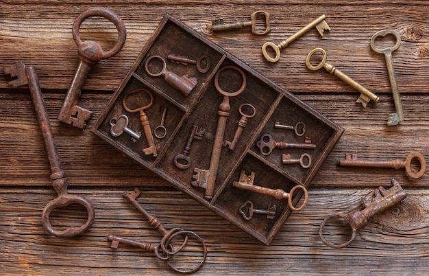 Ancient keys in a wooden box on a vintage wooden background. Premium Photo
