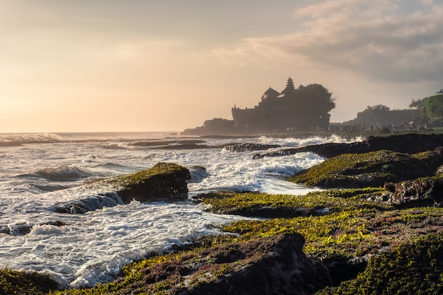 Ancient tanah lot temple on rocky mountain at coastline Premium Photo