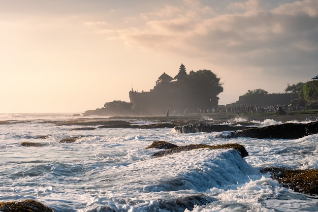 Ancient tanah lot temple on rocky mountain at coastline Premium Photo