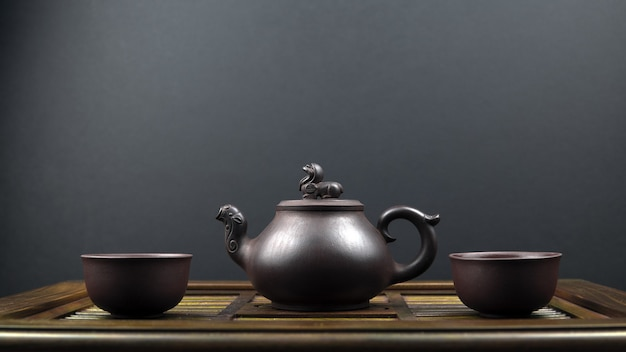 Ancient teapot and two clay bowls on a wooden surface Free Photo