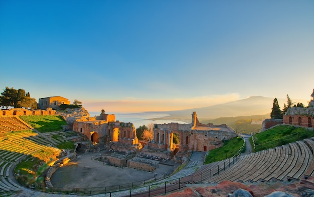 Ancient theatre of taormina with etna erupting volcano at sunset Premium Photo