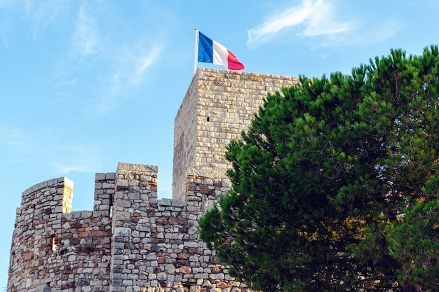 An ancient tower of cannes with the french flag Premium Photo