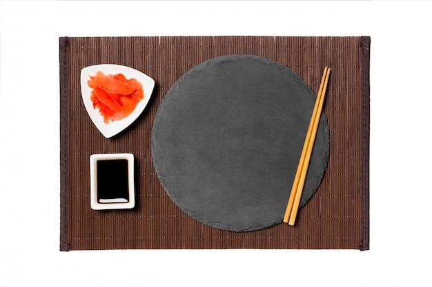 黒い竹のマットの上に寿司、生and、醤油の箸が付いた空の円形のスレート板。 copyspaceのトップビュー Premium写真