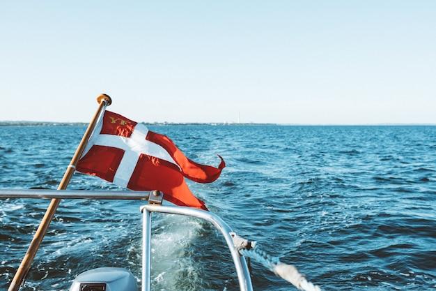 И белый флаг на лодке, плавающей над океаном под голубым небом в дневное время Бесплатные Фотографии
