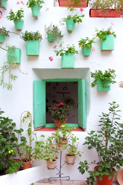 アンダルシアのパティオのファサードには、鉢や吊り下げられた植物で飾られた木製の窓があります。コルドバ、アンダルシア、スペイン。 Premium写真