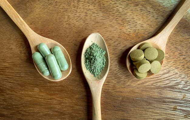 Andrographis paniculata, capsules and powder form on a wooden spoon Premium Photo