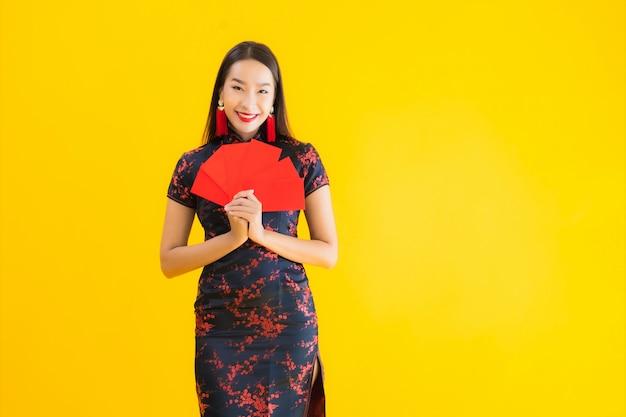 肖像画の美しい若いアジアの女性は、ang paoのチャイナドレスや現金で赤い文字を着る 無料写真