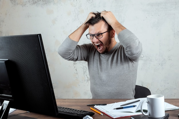 Angered man, a man sitting at a table in the office and screaming in anger Premium Photo