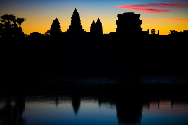 Angkor wat dramatic sky at dawn main facade silhouette reflection on water pond Premium Photo